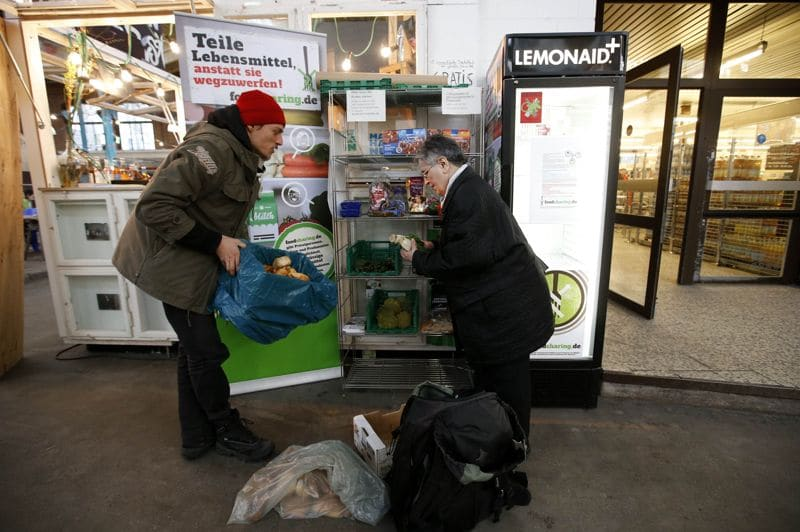 Raphael Fellmer (L), a supporter of the foodsharing movement brings food sorted out from waste bins of an organic supermarket to a distribution point at the indoor market Markthalle Neun (indoor market nine) as a woman takes a piece of bread in Berlin, January 31, 2013. Foodsharing is a German internet based platform where individuals, retailers or producers have the possibility of offering surplus food to consumers for free. Picture taken January 31. TO MATCH STORY GERMANY-FOODSHARING/ REUTERS/Fabrizio Bensch (GERMANY - Tags: FOOD POLITICS SOCIETY)